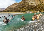 Mustering team heading upriver to begin the autumn merino muster. Horses, musterer's and dog team crossing the upper Shotover River. James Murray, station manager, at right, Branches Station, Shotover Valley, Queenstown Lakes (54411QF00)